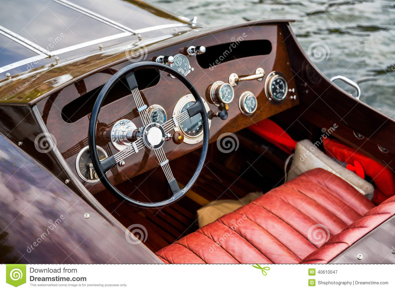 ... of the steering wheel and dashboard of an antique wooden motor boat
