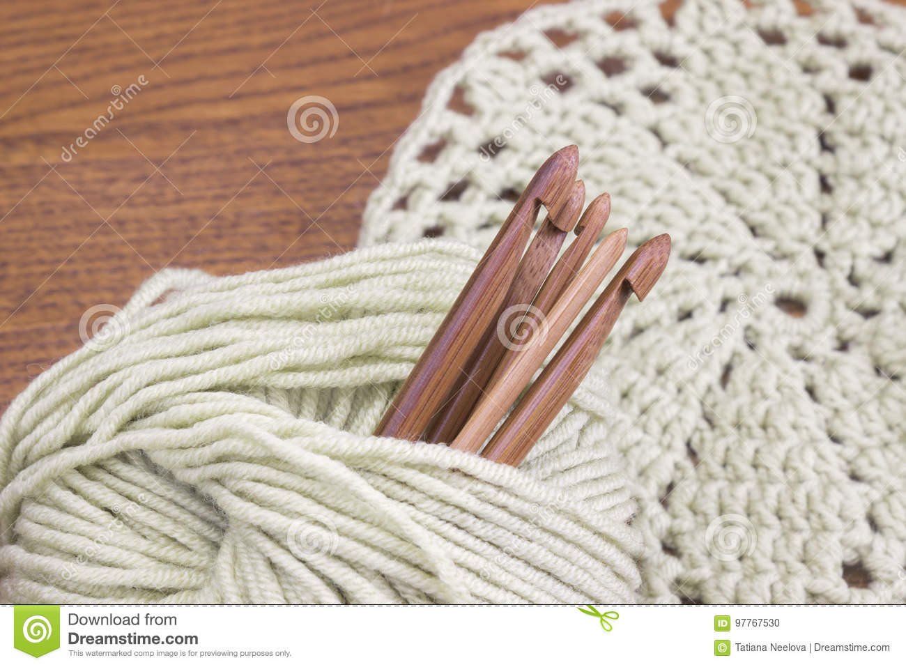 Wooden natural bamboo crochet hooks, doily and yarn ball on the table. Creative work place for homemade crafts. Top view.