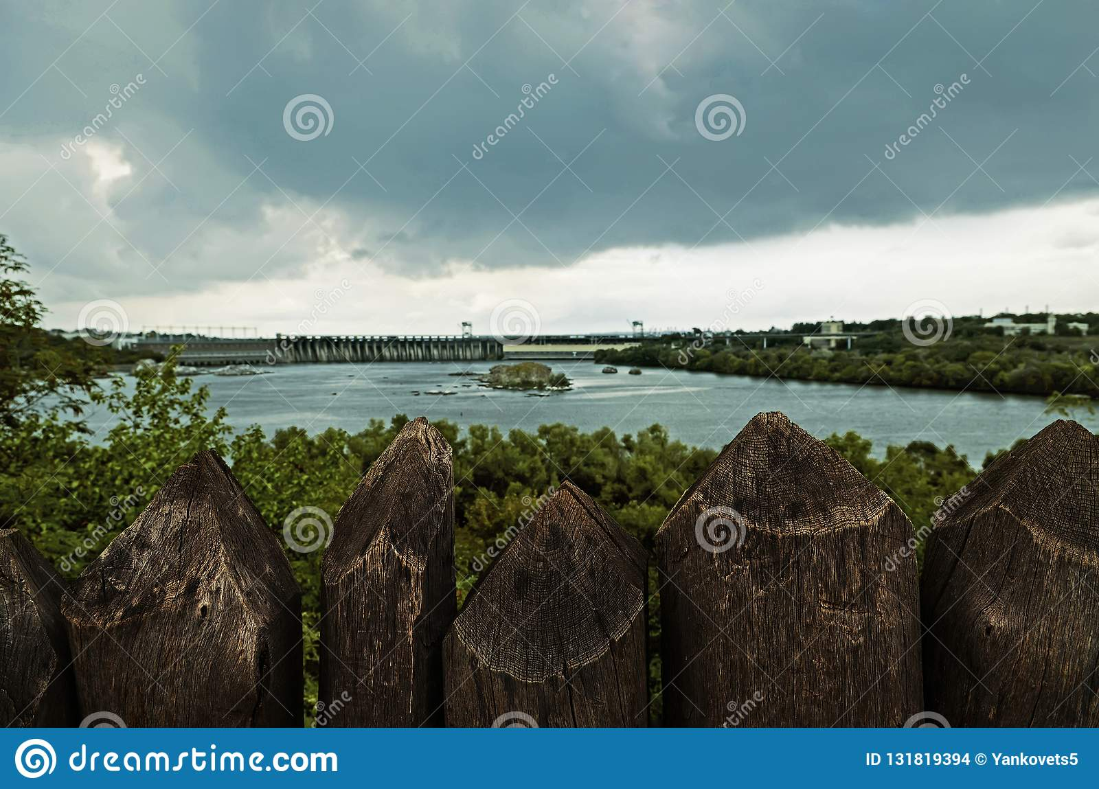Wooden palisade stands against the backdrop of a hydroelectric dam under a dark stormy sky