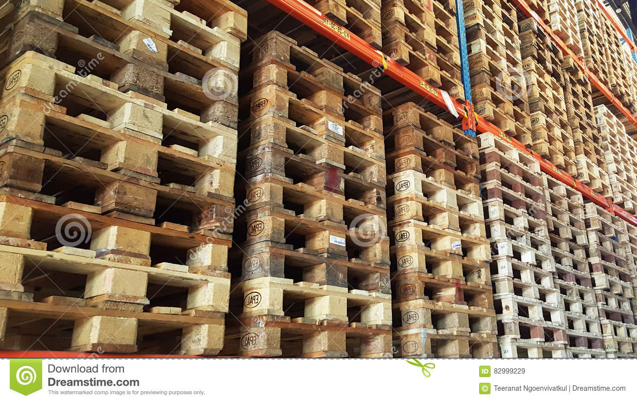 Wooden pallets for product distribution and transportation are stacked in rack of warehouse