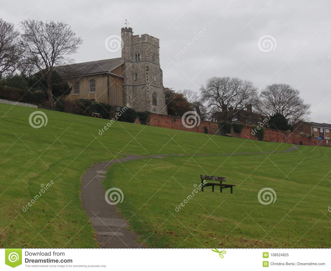 Wooden Park Bench In A Field Overlooking The Church Stock Image
