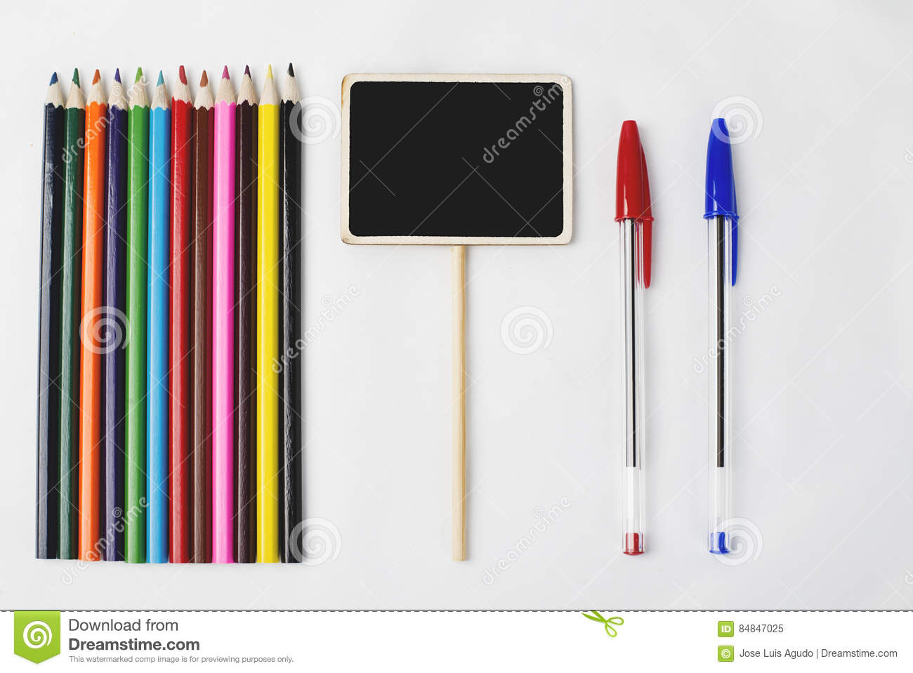 Wooden Pencils Next And Two Pen To Small Square Blackboard On White
