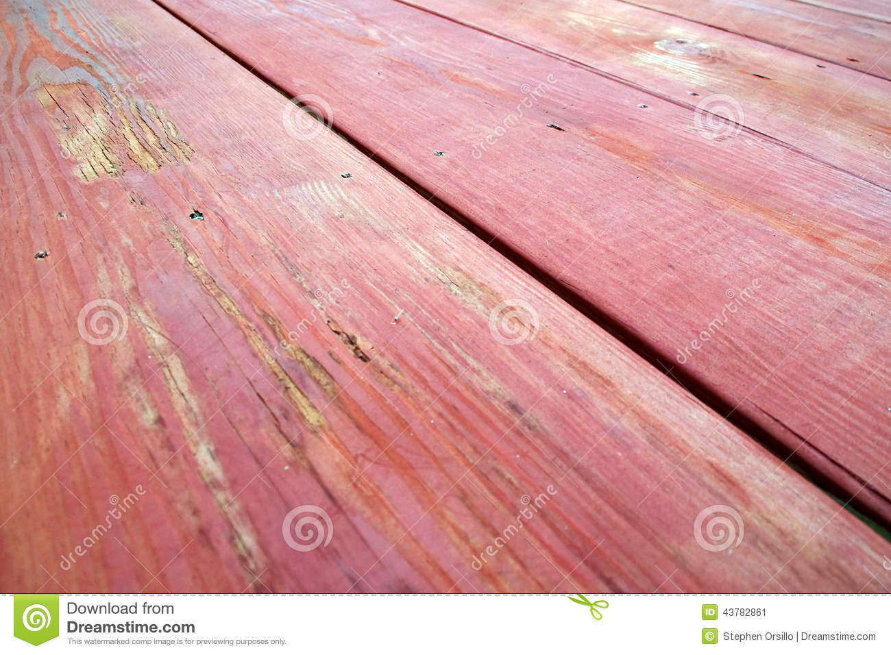 ... down the length of a red stained wooden picnic table in perspective