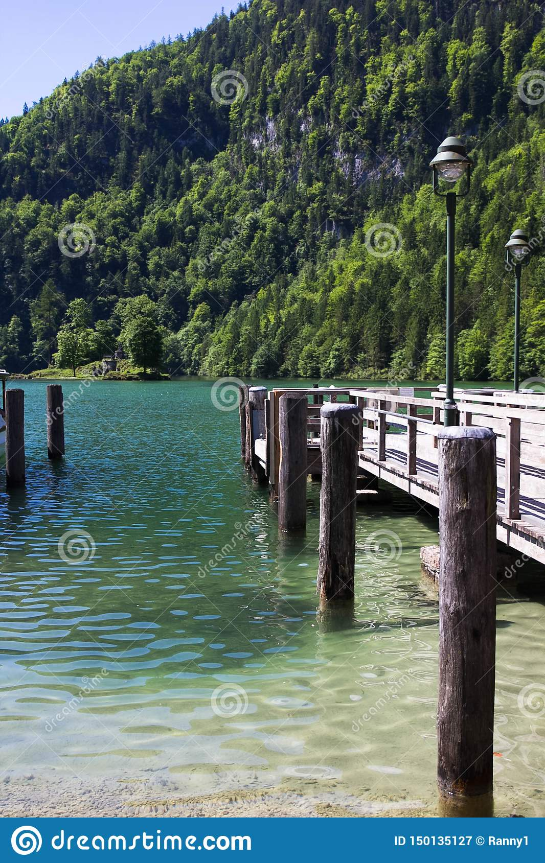 Wooden pier on a lake in the Alps in spring against the backdrop of mountains