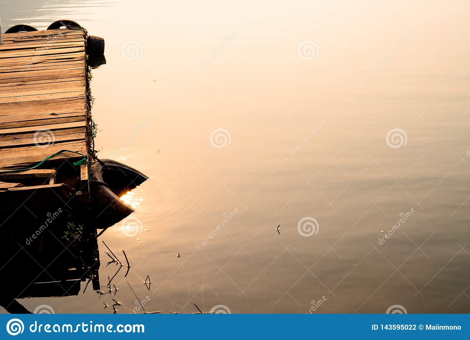Wooden pontoon surrounded with lifebuoy floating on ripple water surface with reflection of sun light during sunrise.
