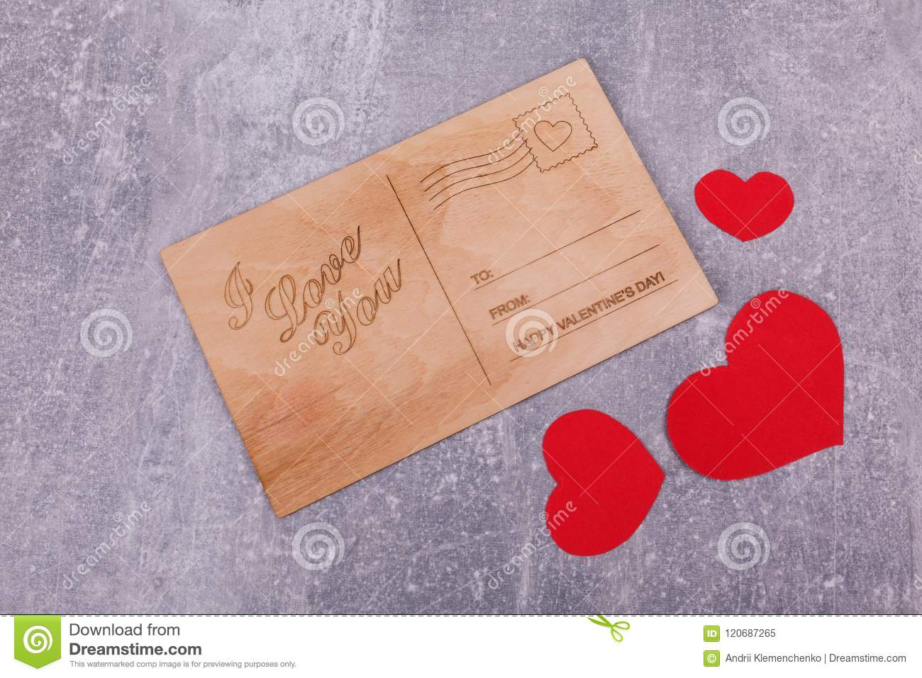 A wooden postcard with red hearts
