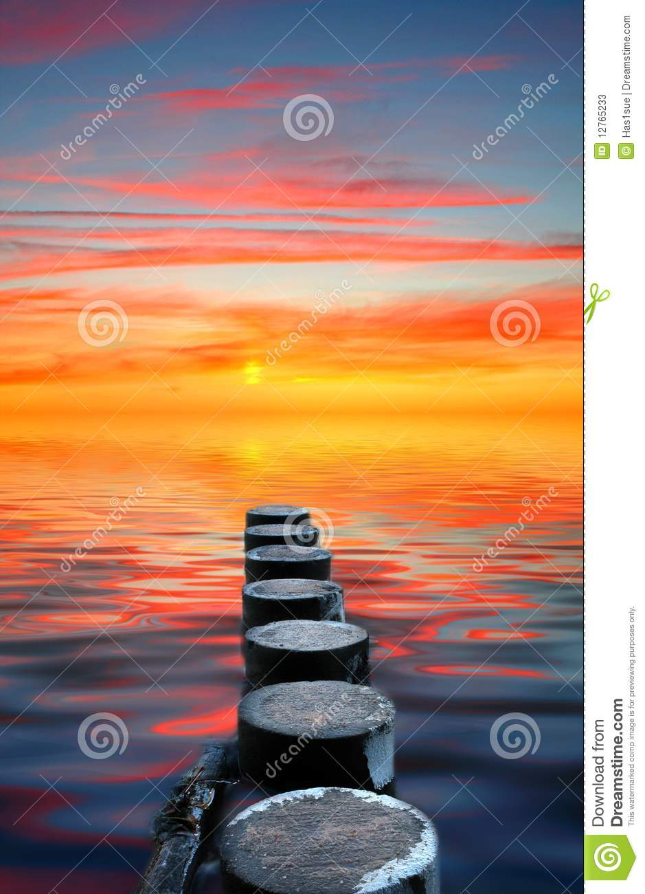 Wooden posts and ocean sunset