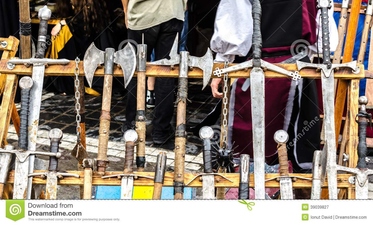 A Wooden Rack With Several Medieval Weapons Stock Photo