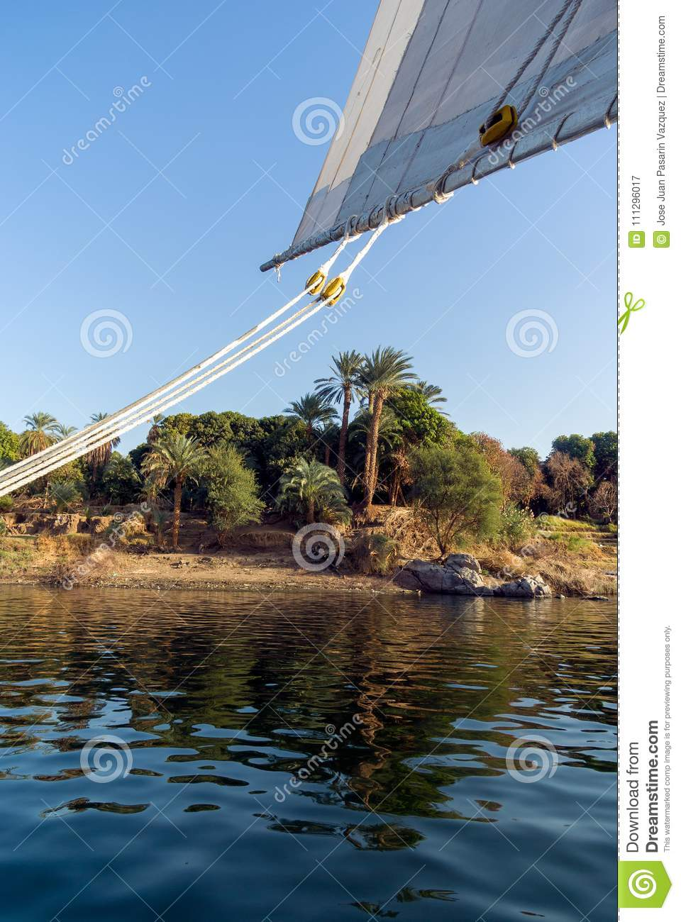 Wooden ropes and pulleys of the sail of a typical boat called Felucca on the Nile River in Africa, with shores lined with palm tre