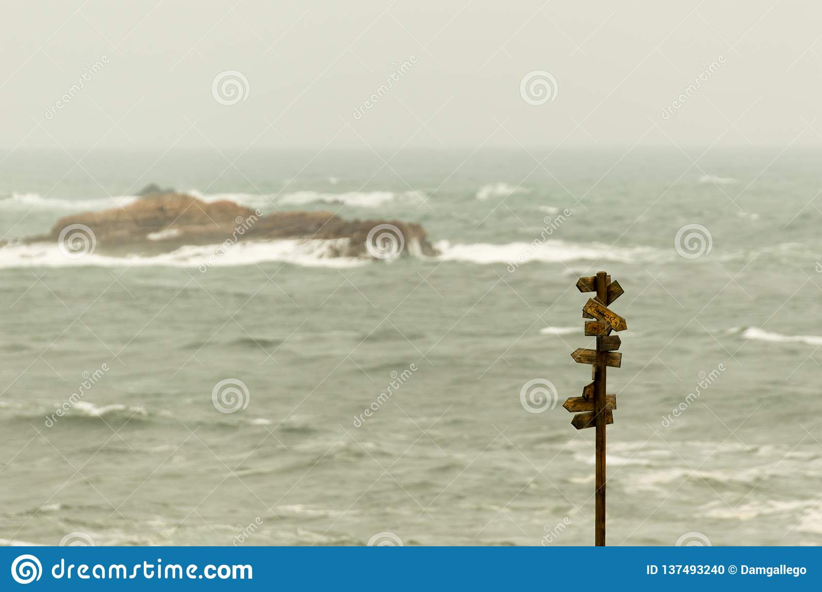 Wooden signpost with many pointers with the sea at background