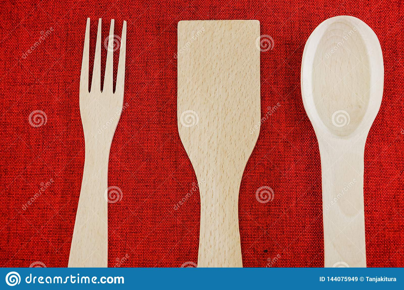 Wooden spoons, fork and spatula on a red background. View from above