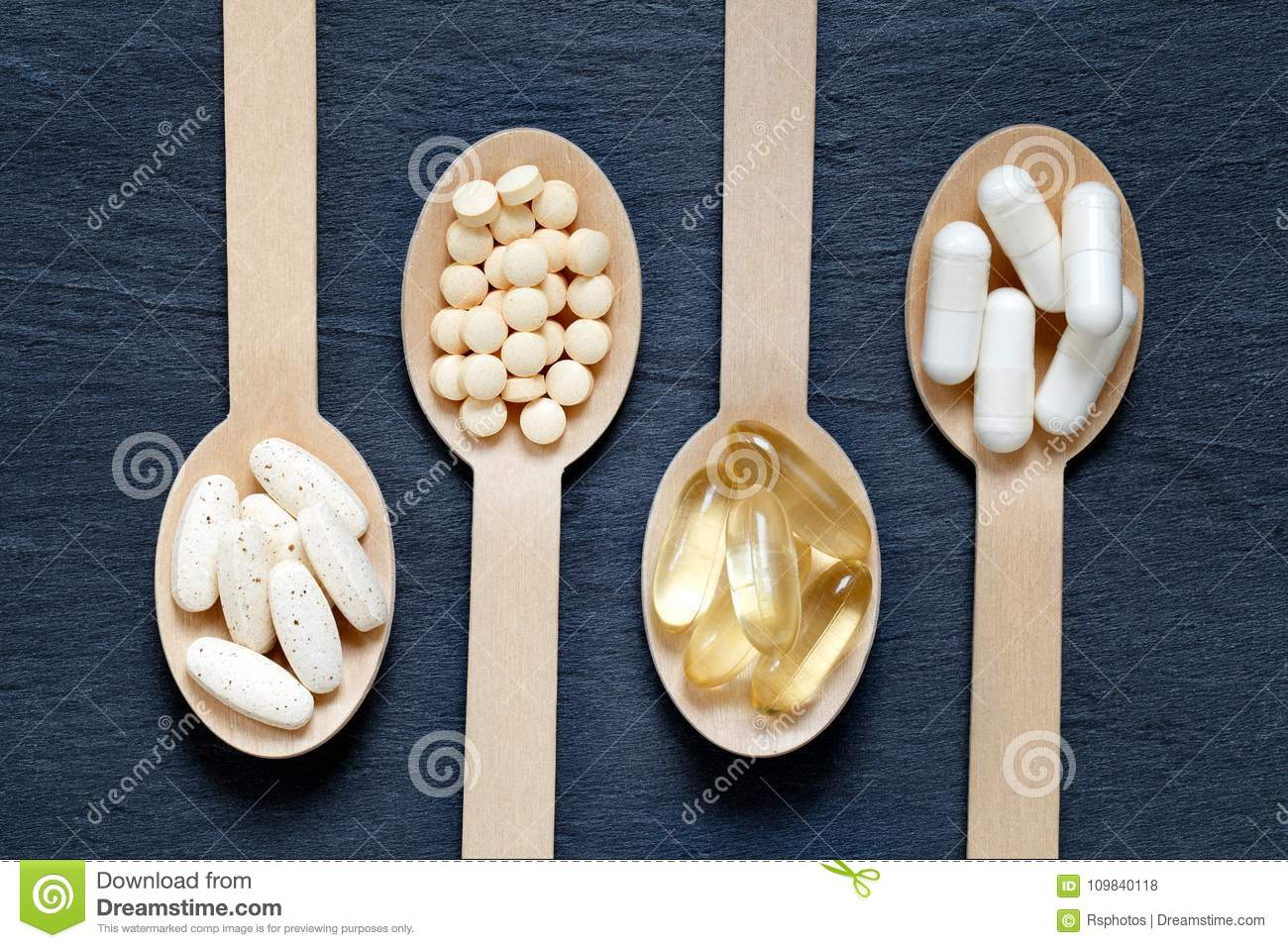 Different healthy supplements on wooden spoons