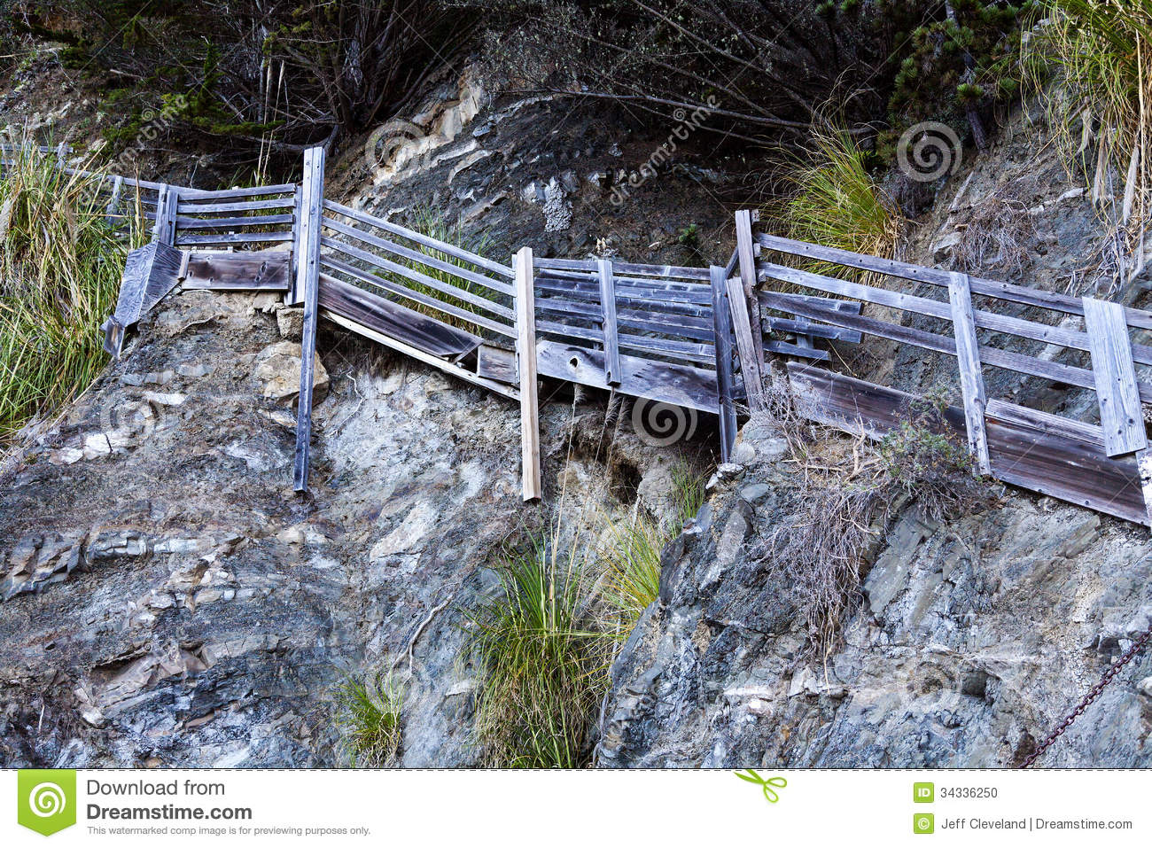 Wooden stairs going up cliff wall beach stock photo