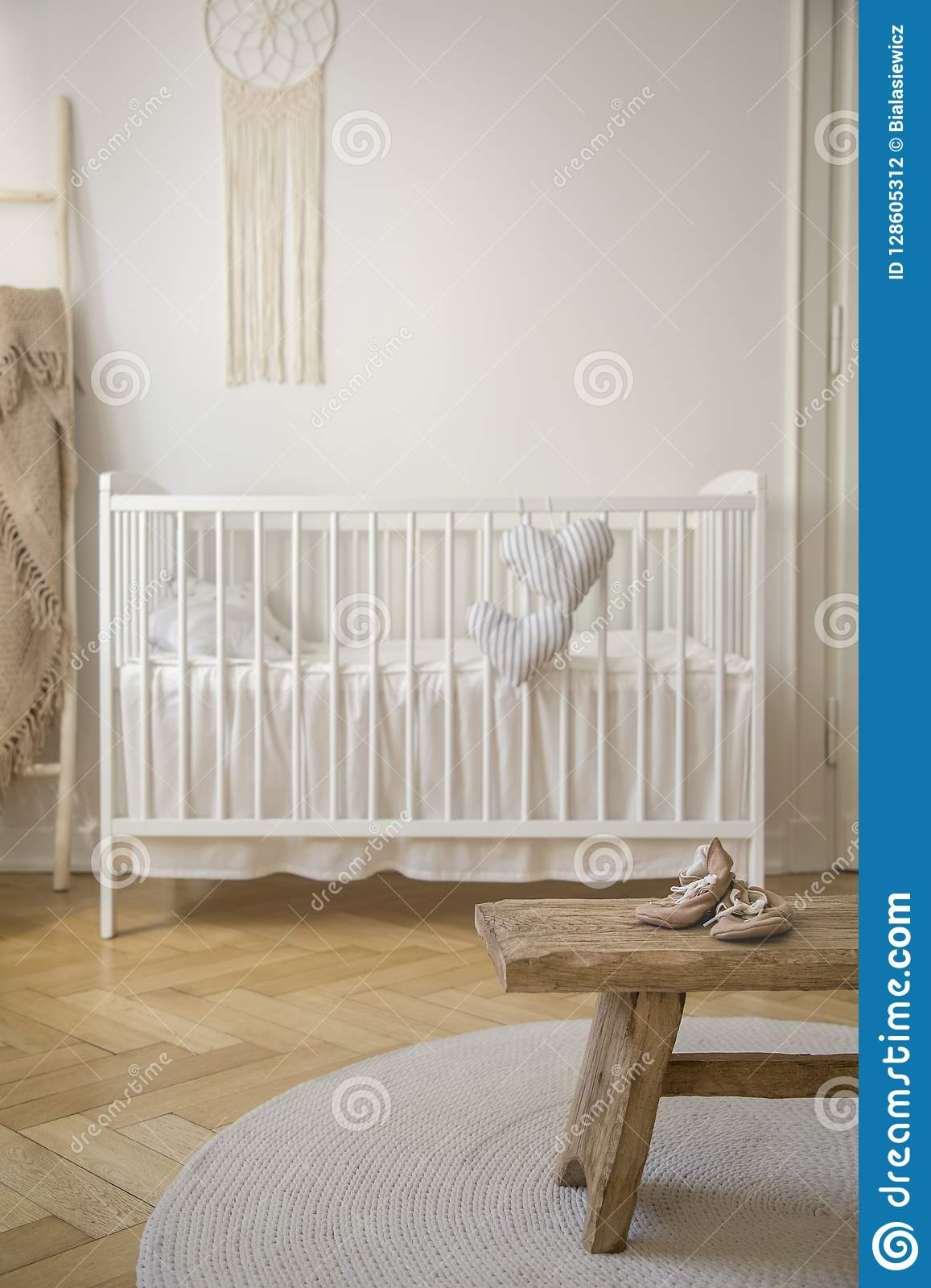 Wooden stool with shoes on round rug in bright baby`s bedroom interior with white cradle