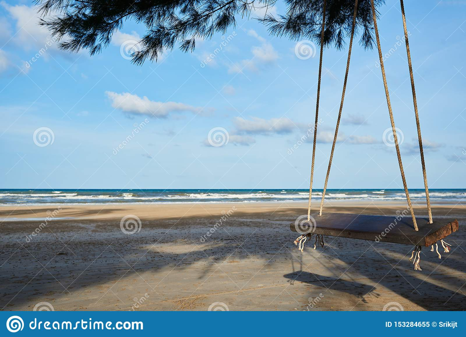 A wooden swing on the beautiful blue sky and sea background