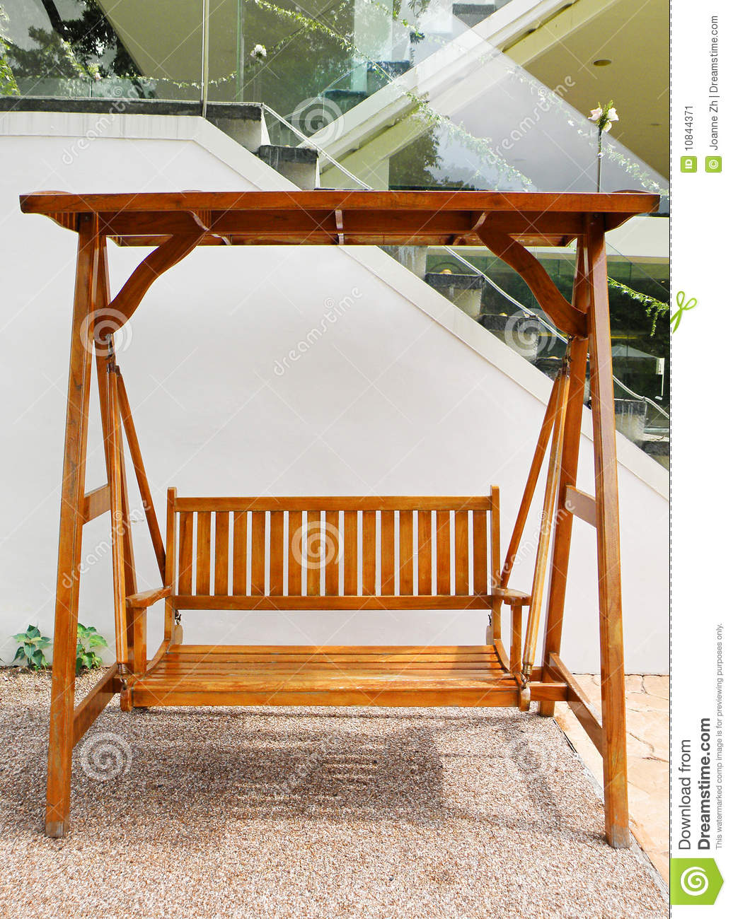 wood swing with double seating, placed outdoors on the patio. Garden ...