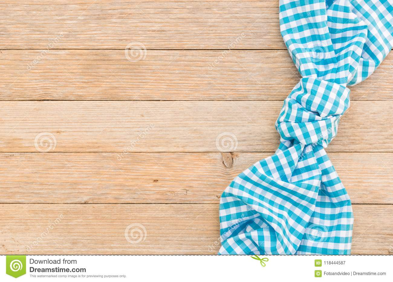 Checked blue napkin on wood table background, top view, copy space