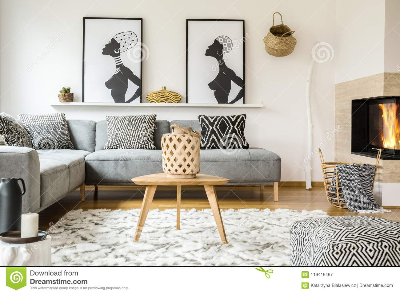 Wooden table on carpet in african living room interior with patterned cushions on grey sofa. Real photo