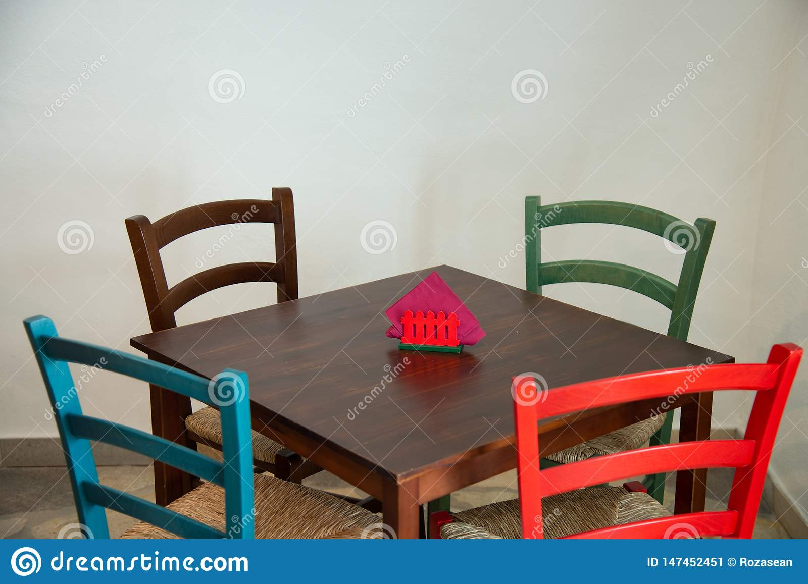 Wooden Table With Colorful Chairs In A Restaurant Stock