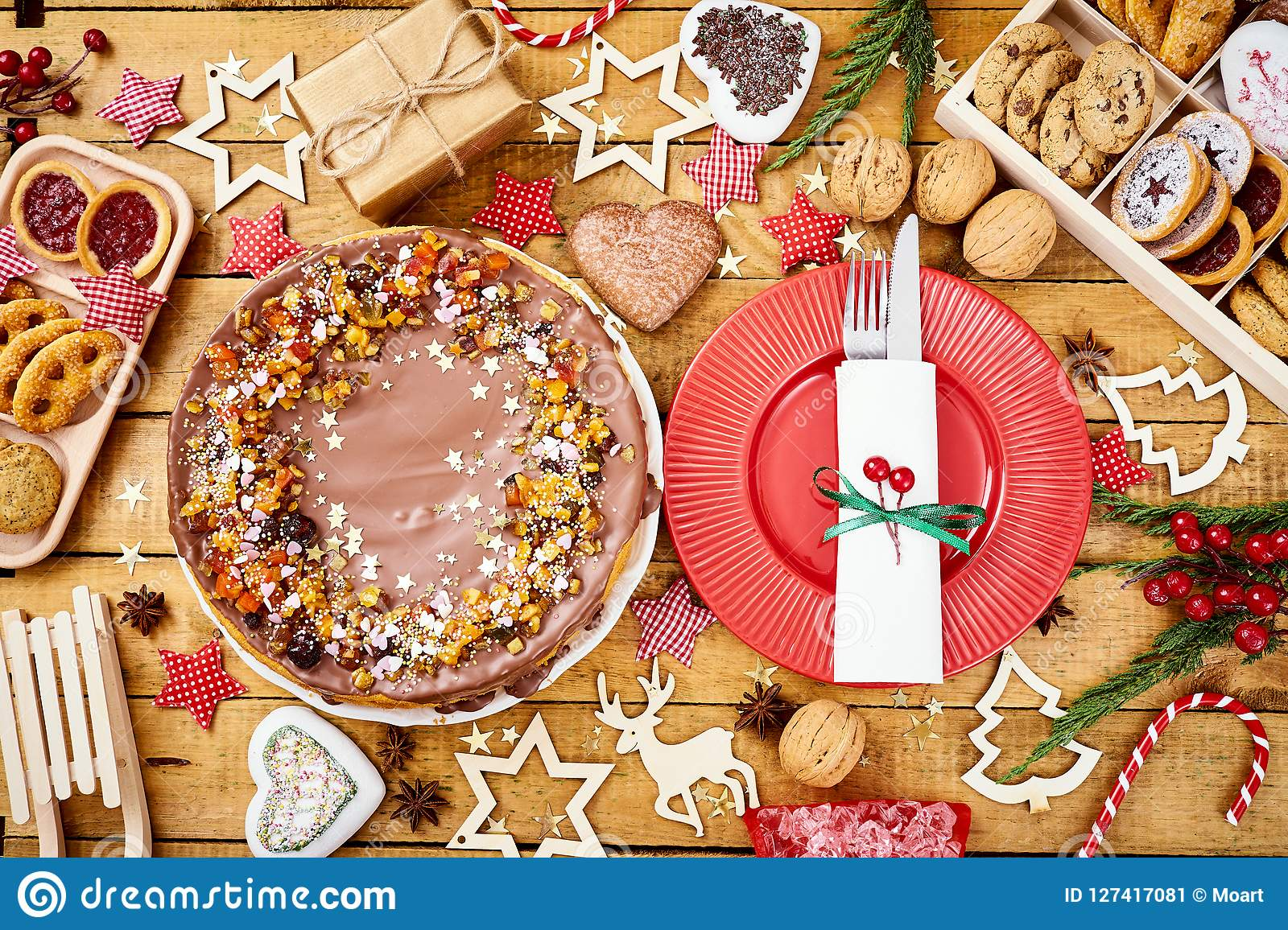 Wooden table with delicious Christmas cake decorations and different cookies