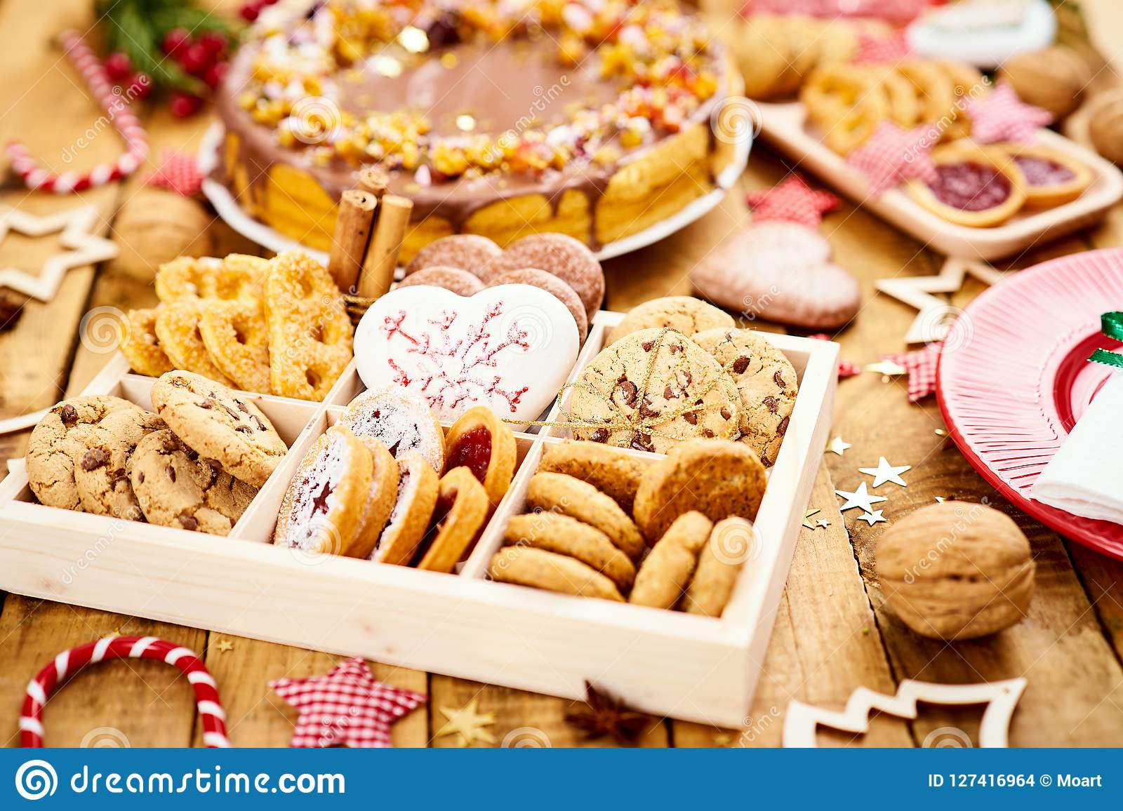 Wooden Table With Delicious Christmas Cookies In A Box And Various