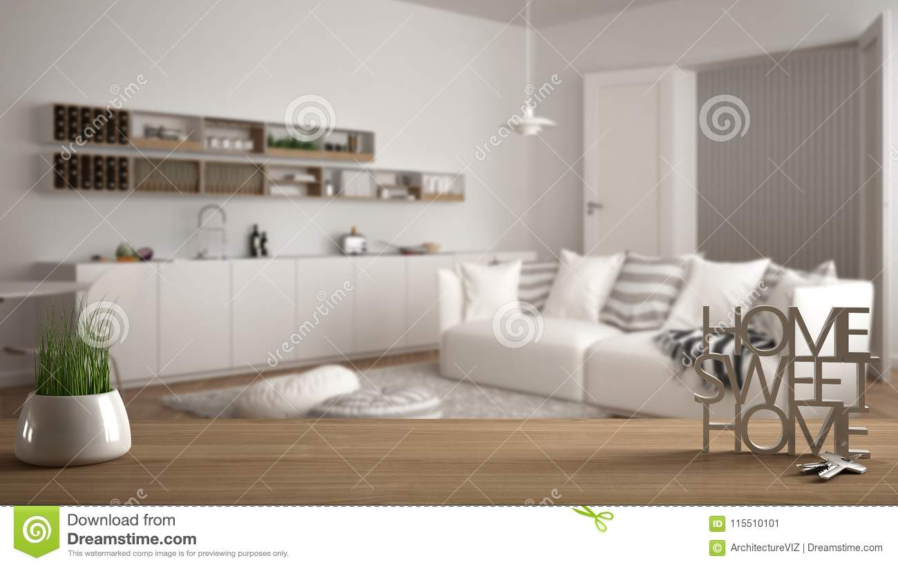 Wooden table desk or shelf with potted grass plant house keys and 3d letters making the words home sweet home over modern white living room
