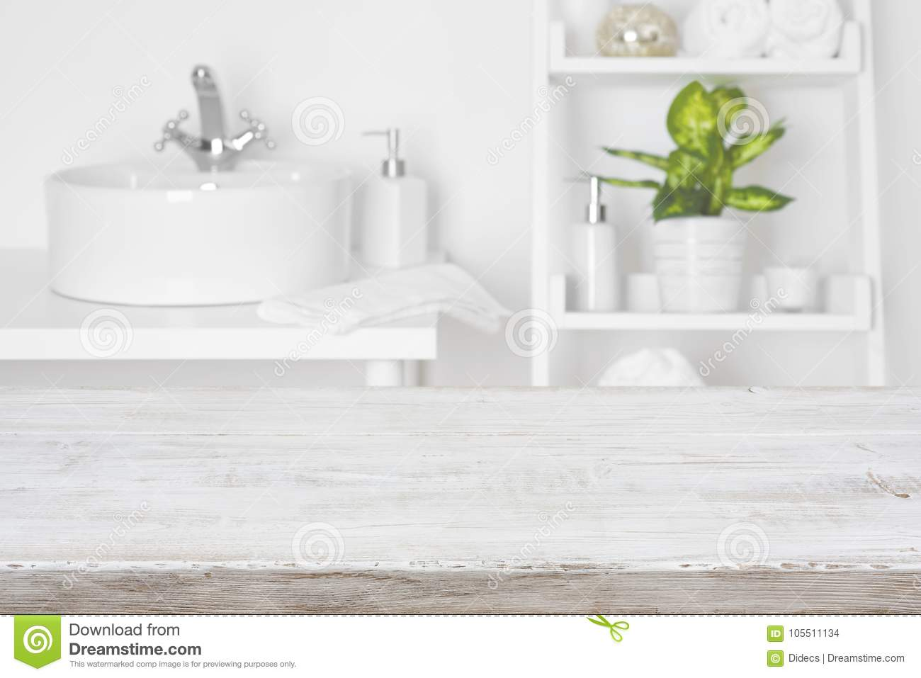 Wooden Table In Front Of Blurred White Bathroom Shelves