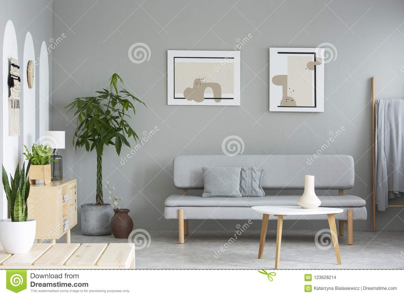 wooden table in front of grey sofa in simple living room interior rh dreamstime com there is a table in front of the sofa there is a table in front of the sofa