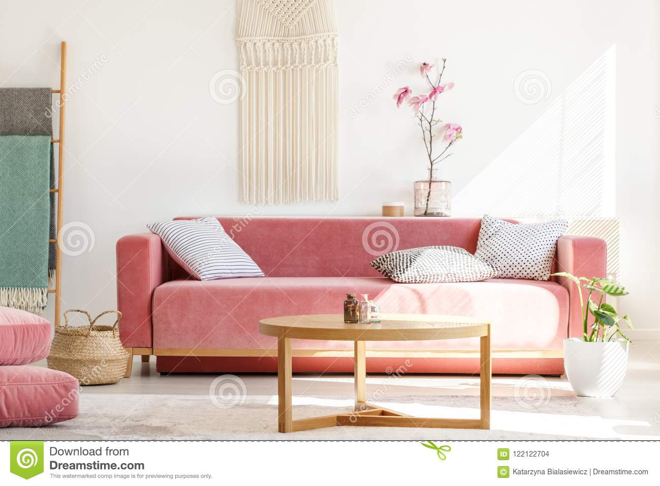 Wooden table in front of red sofa in pastel living room interior