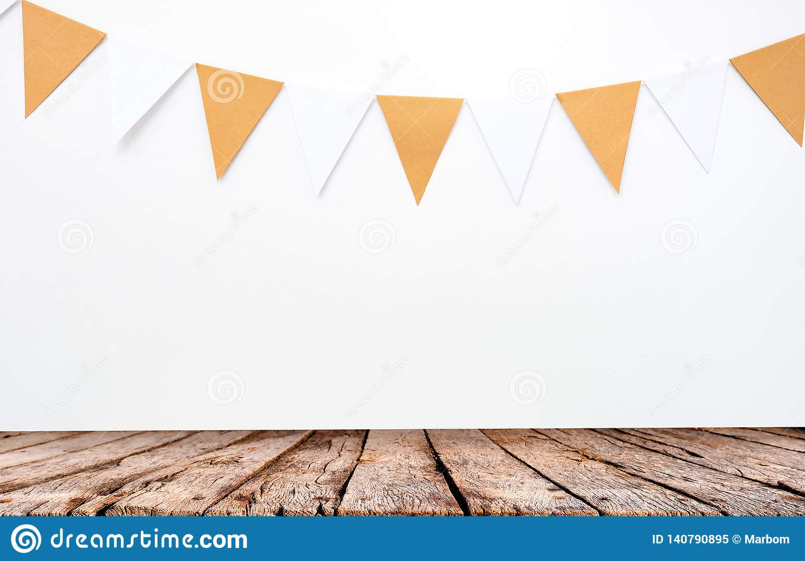 Wooden table and hanging paper flags on white wall background, decor items for party, festival, celebrate event