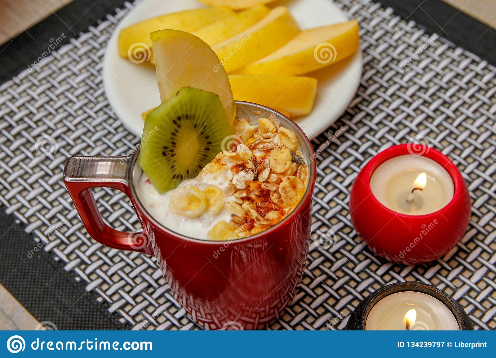 Healthy food, various seeds, integral cereals and dried fruits in yogurt. Fresh fruit, apple, kiwi and persimmon