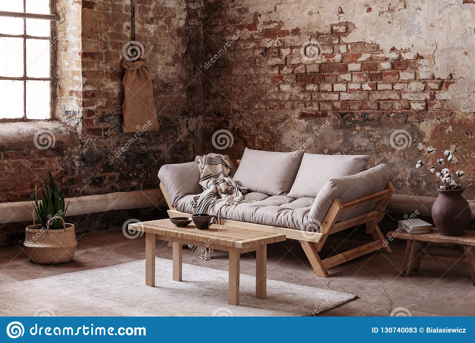 Wooden Table On Rug In Front Of Beige Couch In Apartment