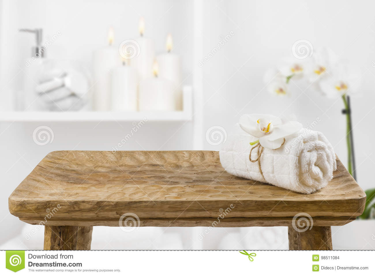 Wooden table with spa towel on blurred bathroom shelf background
