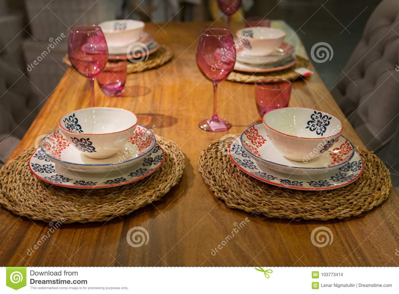 Wooden table with wine glasses and ceramic dishes
