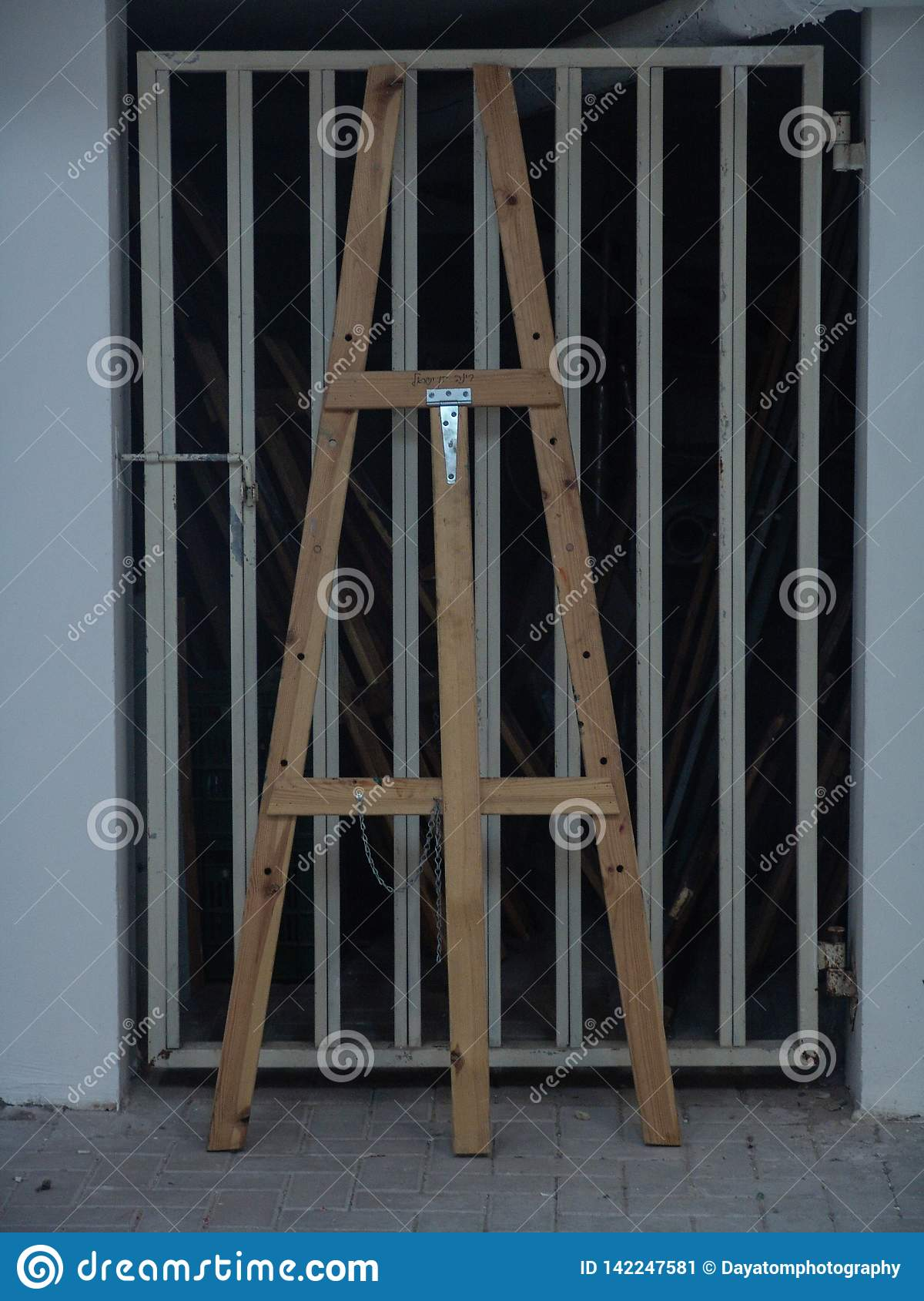 Wooden tall easel standing against a metal garage door in white