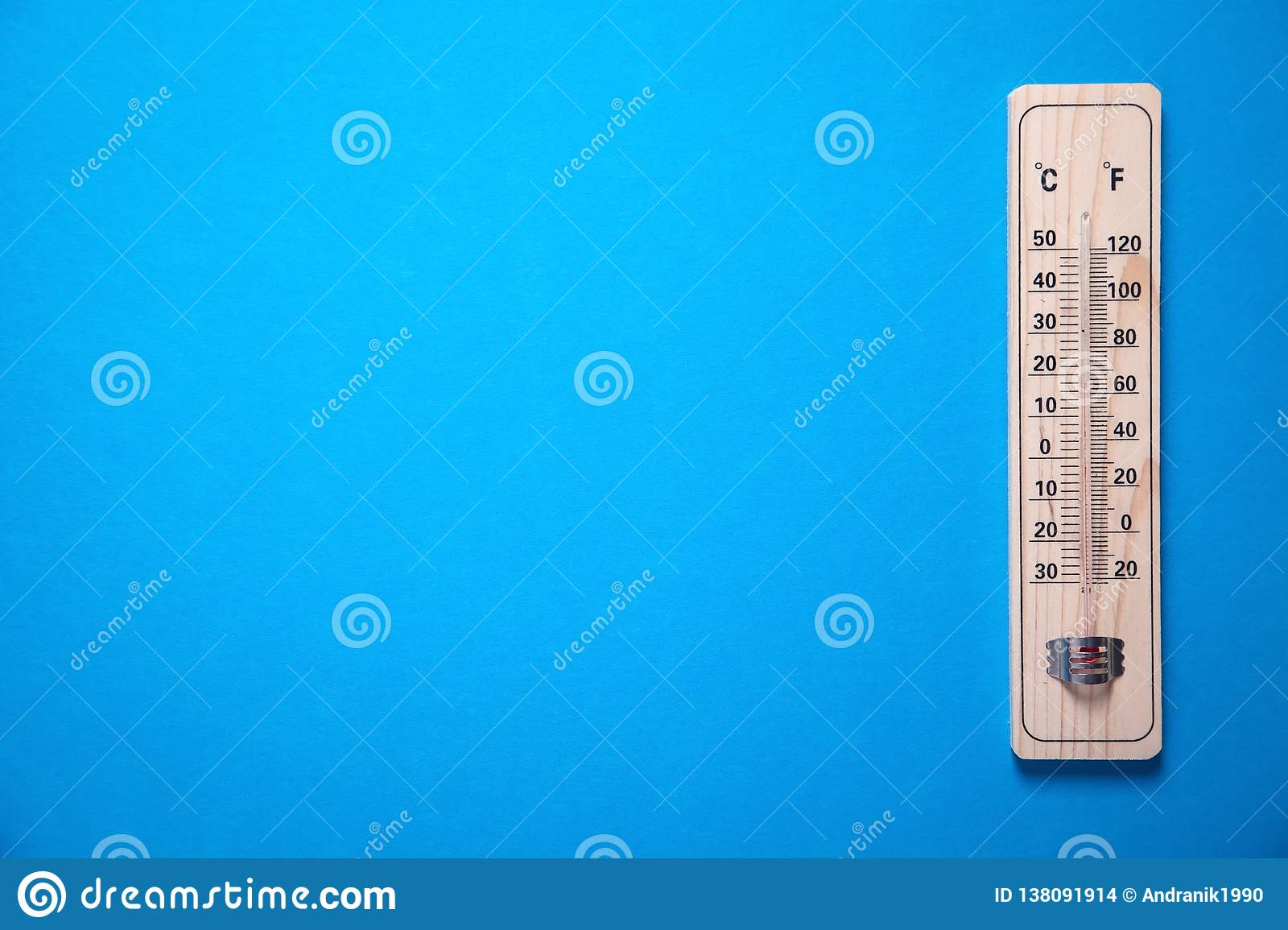 Wooden thermometer on blue background