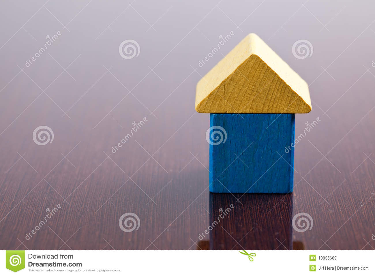 Wooden toy block house on wooden table.