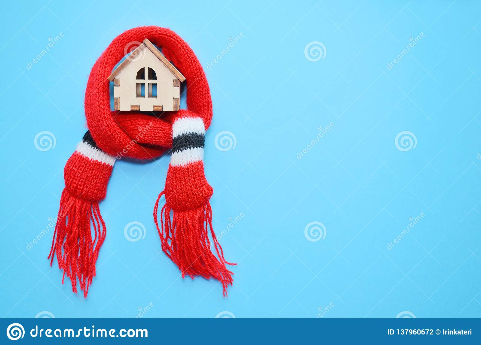 Wooden toy house with windows in a red scarf on a blue background, warm house, insulation of house, copyspace