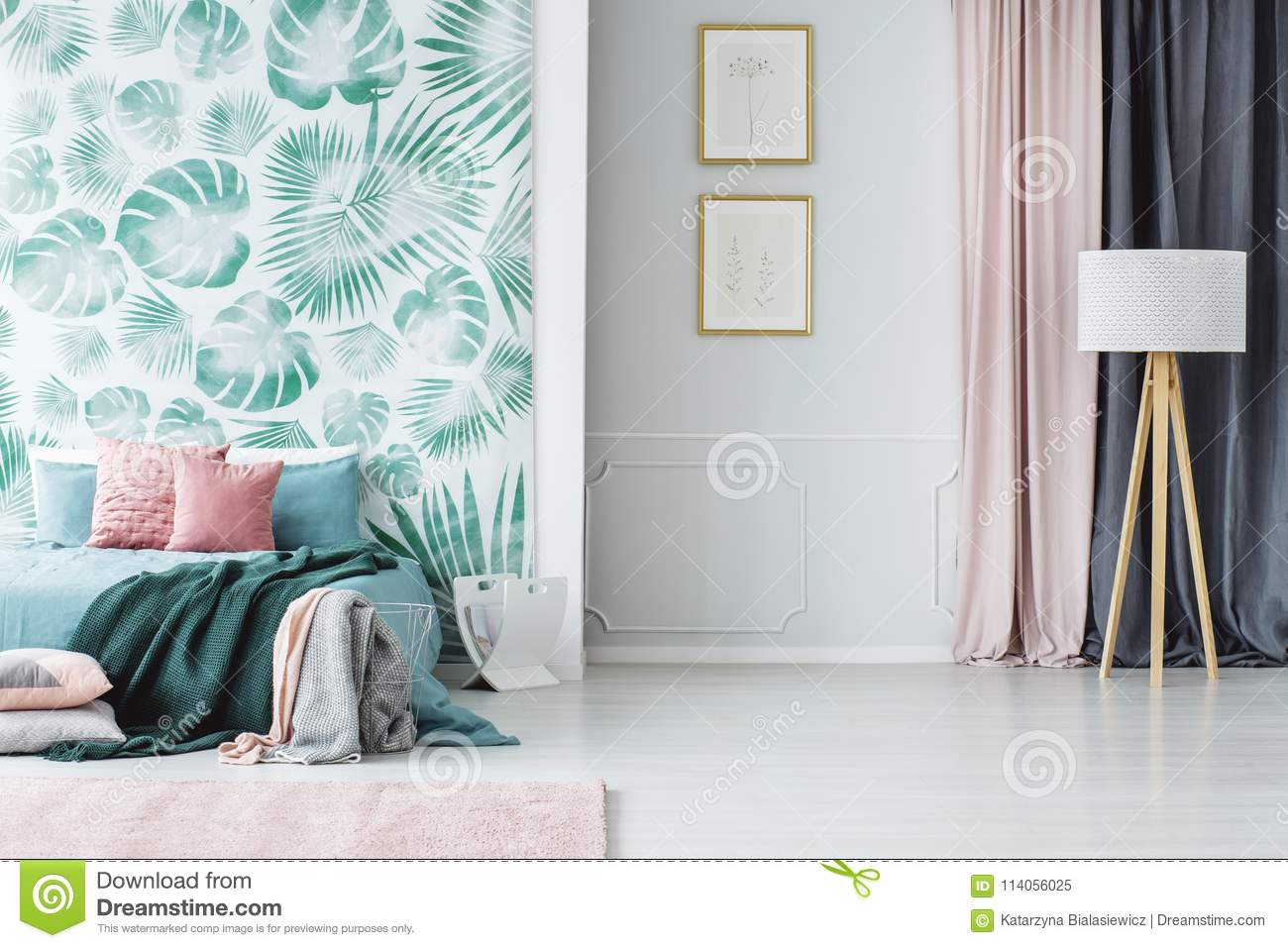 8b9acea0dd5 Wooden tripod floor lamp and a big bed with pillows and blankets in a cozy  pale green and pink bedroom interior