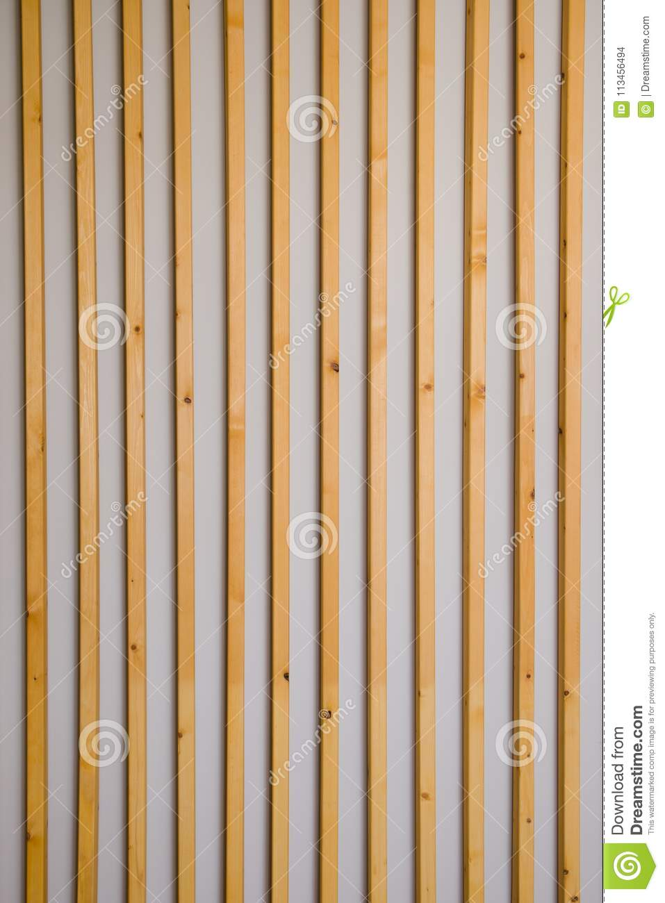 Wooden vertical slats batten on a light gray wall background. Interior detail, texture, background. The concept of minimalism and