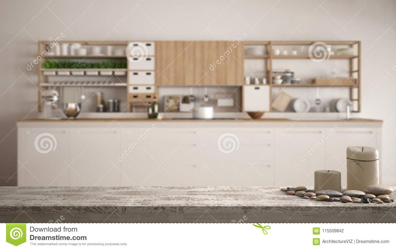 Wooden vintage table top or shelf with candles and pebbles, zen mood, over blurred empty minimalist white wooden kitchen closeup,