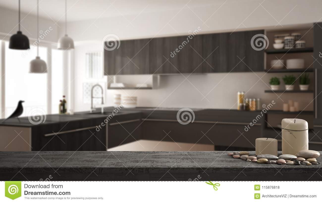 Wooden vintage table top or shelf with candles and pebbles, zen mood, over blurred modern minimalistic kitchen, gray architecture