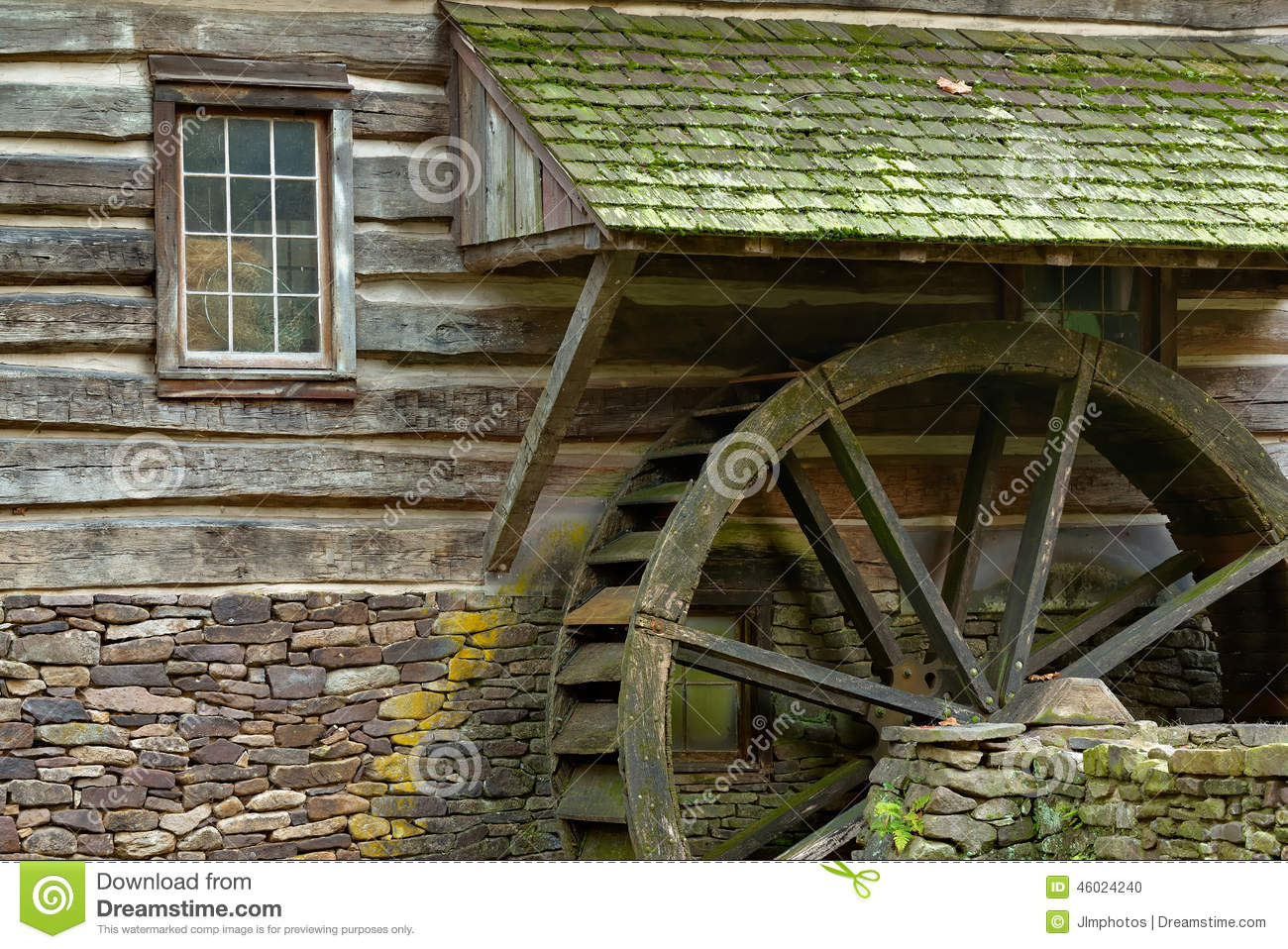 Wooden water paddle wheel and mossy stones on the side of a old