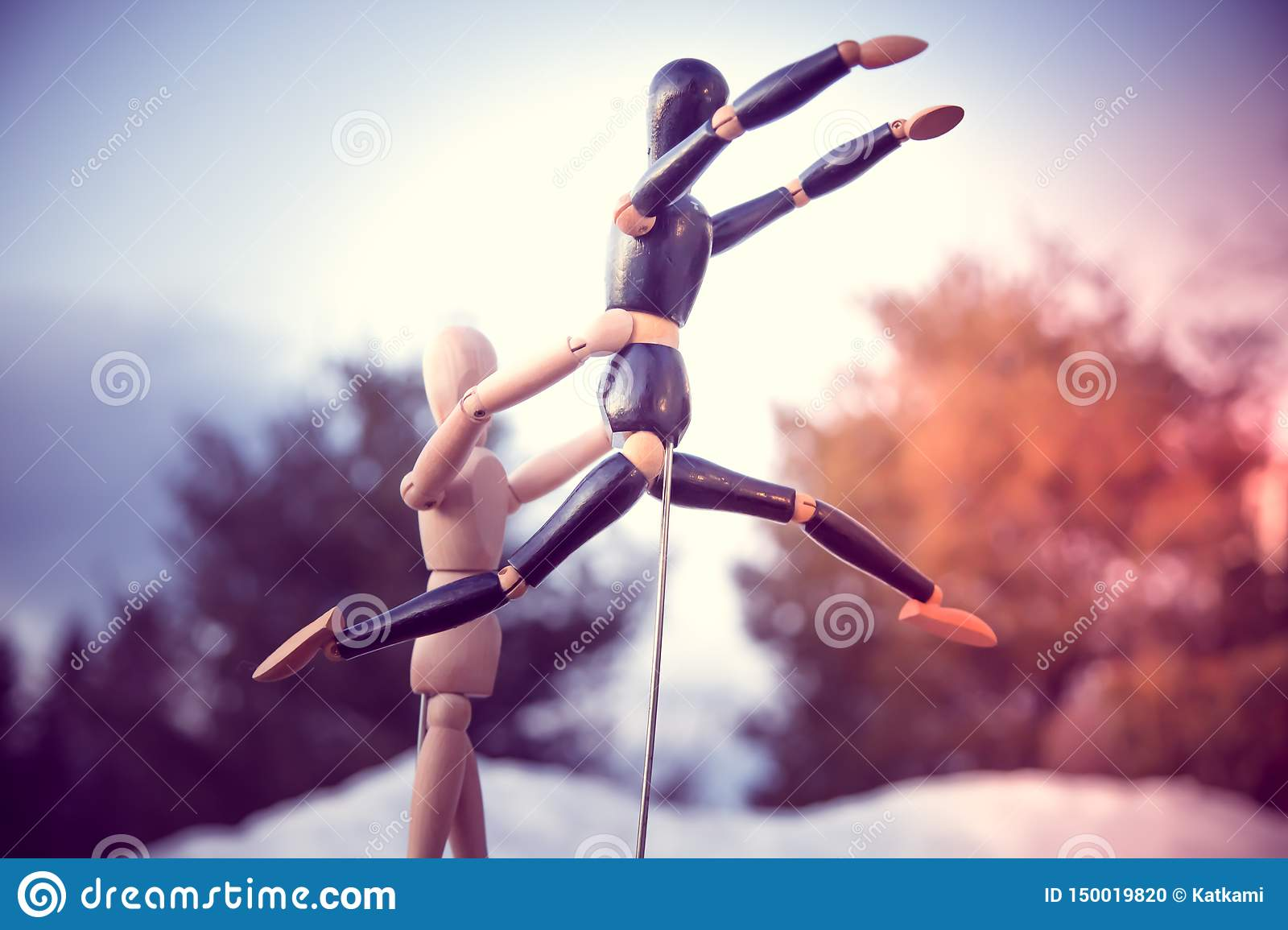 Wooden mannequin helping other mannequin jump