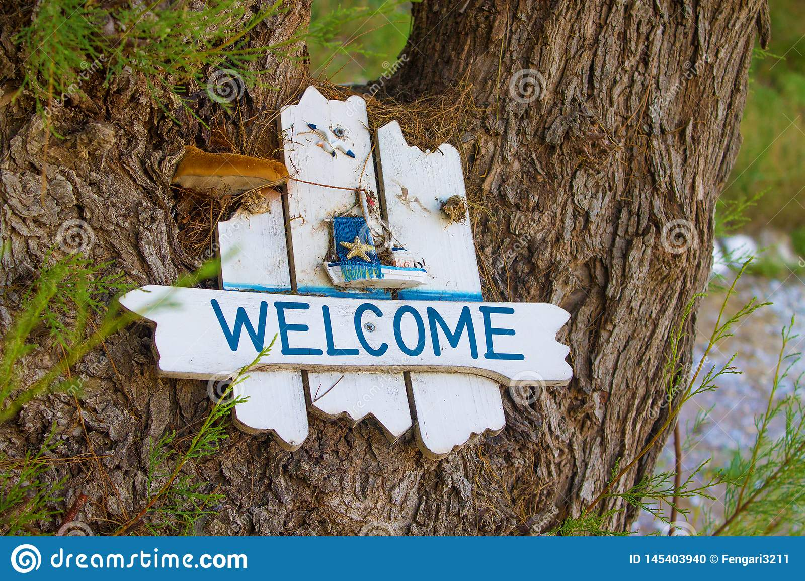 Wooden white plaque with the inscription welcome to the tree with branches