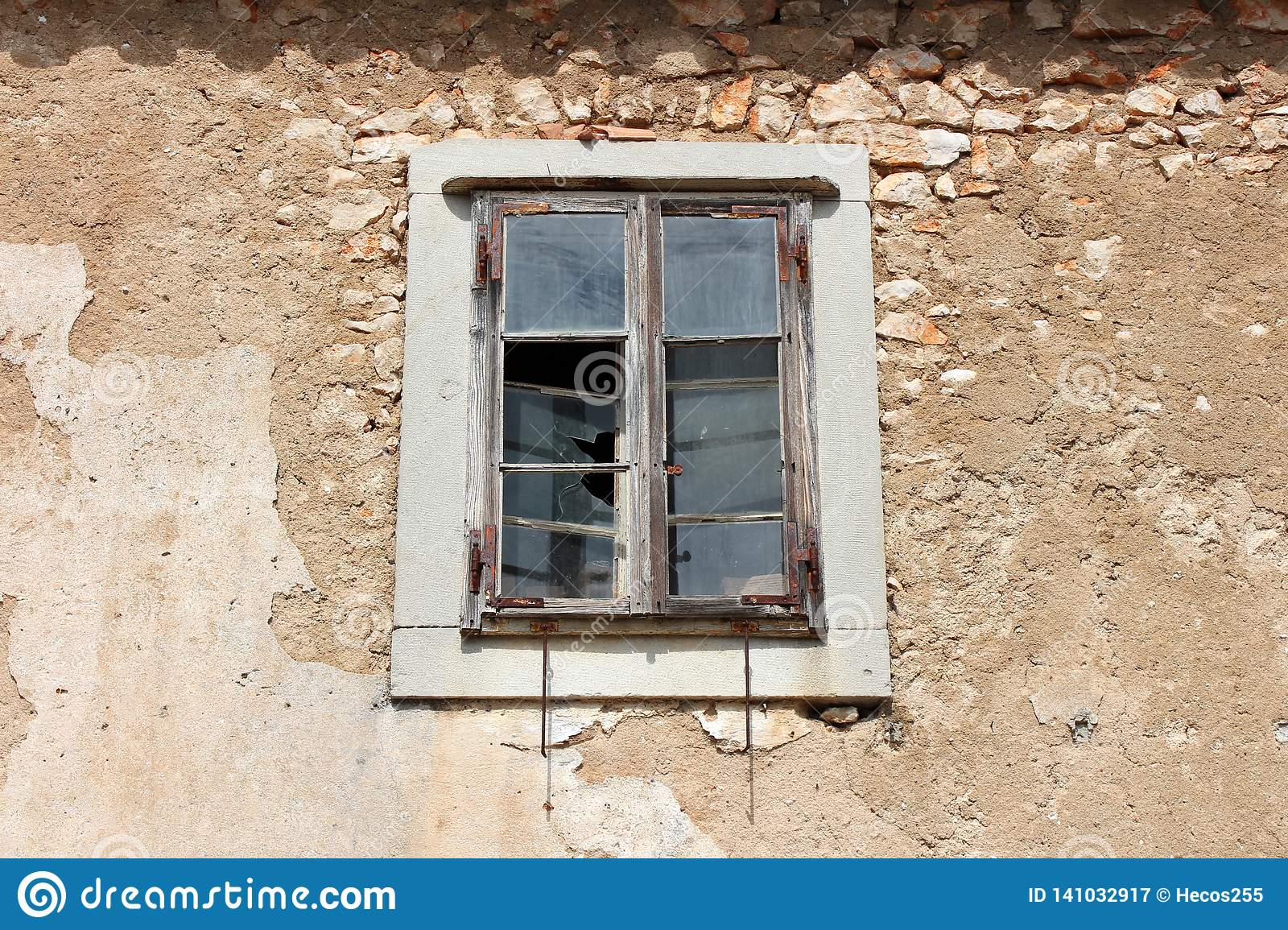 Wooden window on abandoned house with broken glass mounted on cracked frame with rusted metal hinges surrounded with facade and
