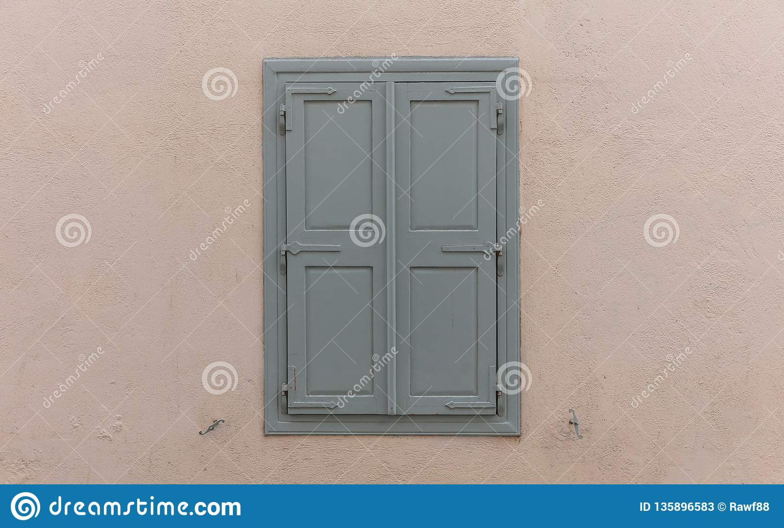 Wooden Window With Grey Shutters Closed On Painted Wall