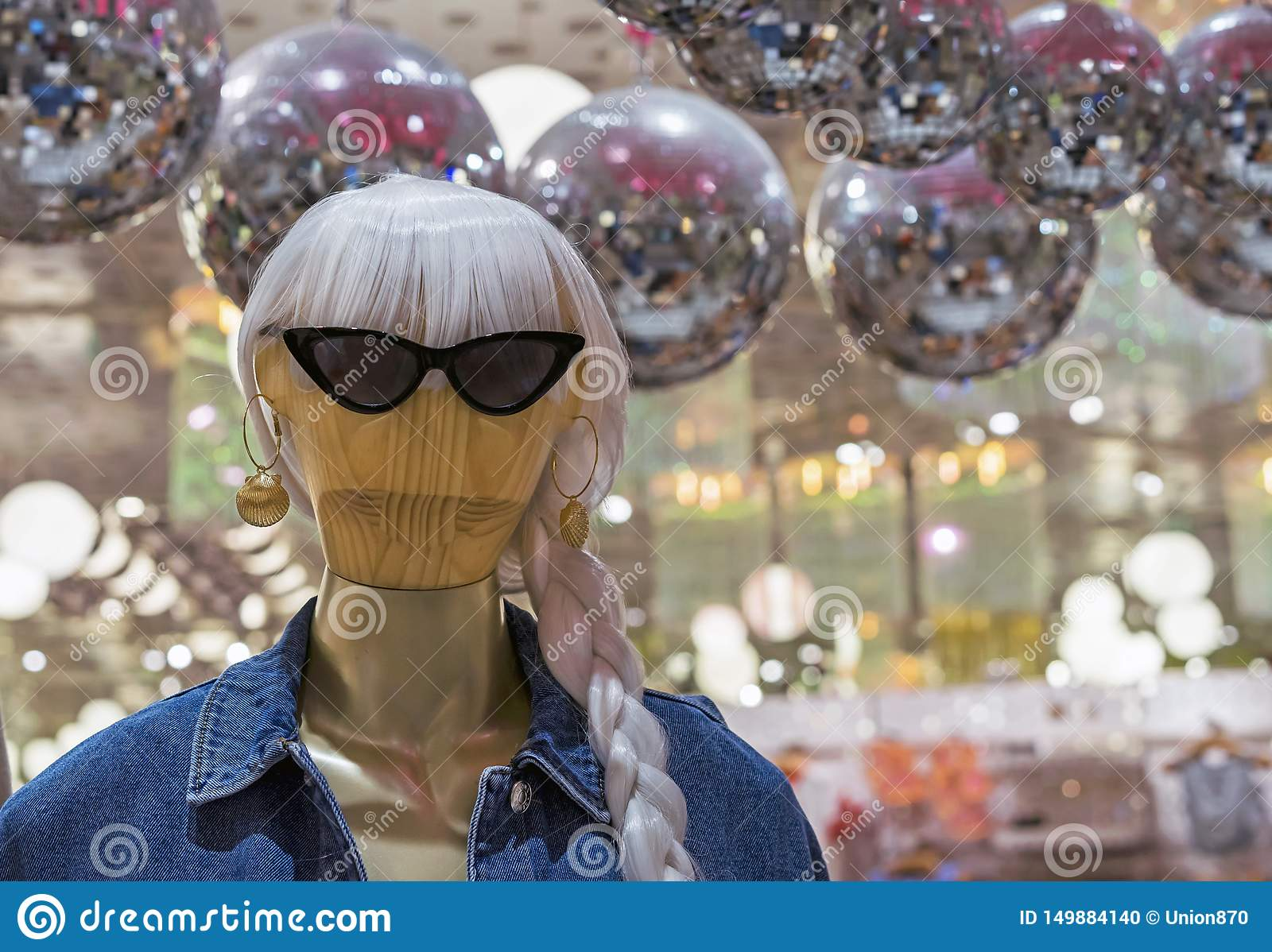 Wooden women`s mannequin in a jeans jacket and sunglasses