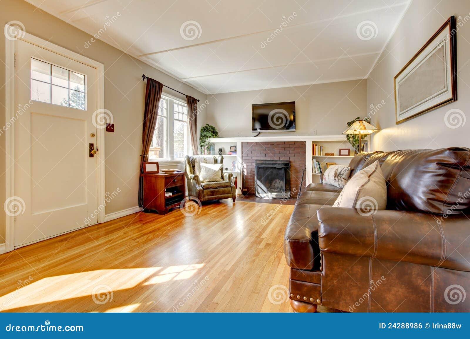 Woonkamer met beige muren, leerbank en tv. royalty vrije stock ...