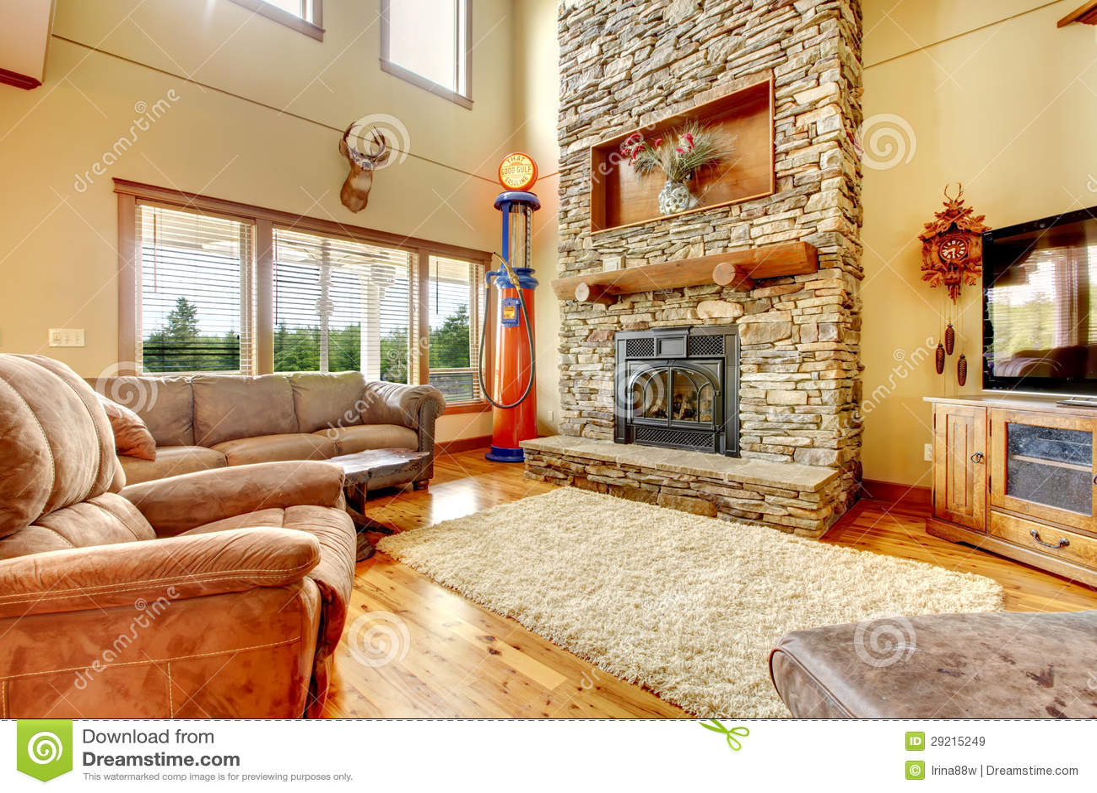 Woonkamer met hoog plafond, steenopen haard en leerbank. royalty ...